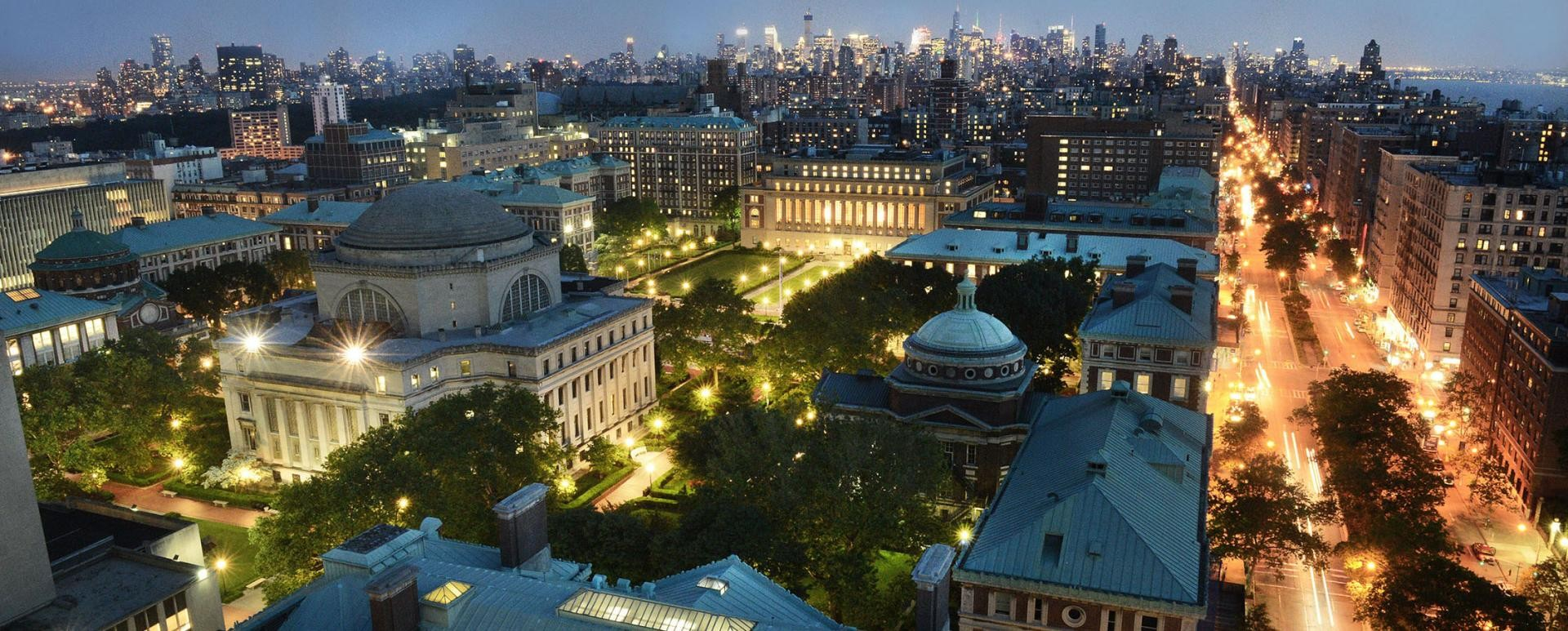 Angled view of Columbia's Morningside Heights campus at night with the Manhattan skyline in the background